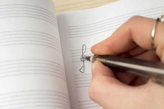 譜面にト音記号を書き込む画像